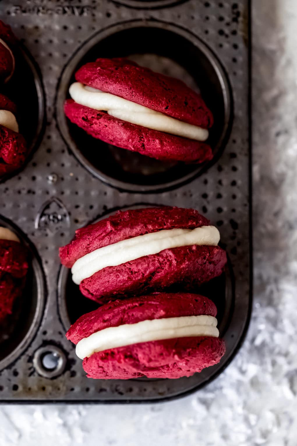 three red velvet whoopie pies in a muffin tin