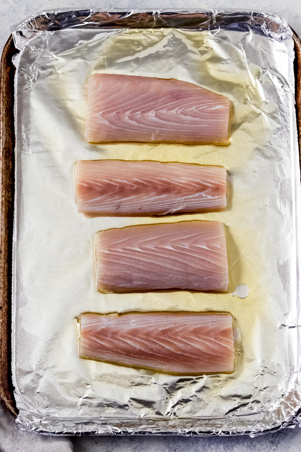 raw mahi mahi fillets on a foil lined sheet pan