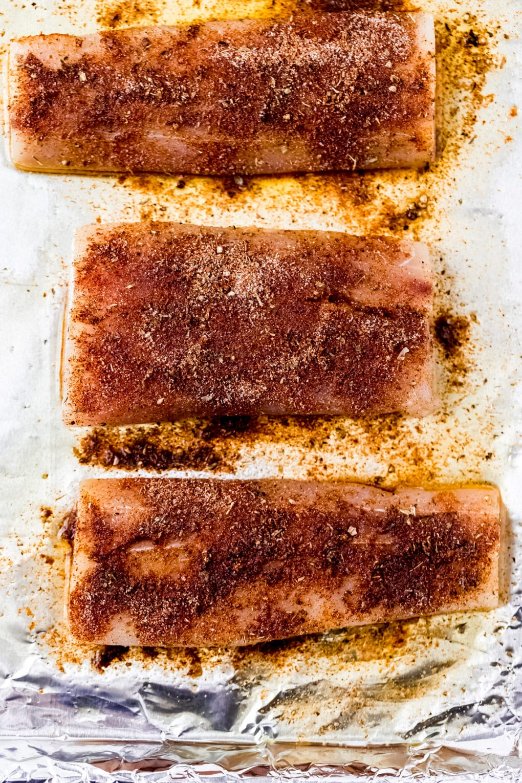 raw mahi mahi fillets coated in blackened seasoning