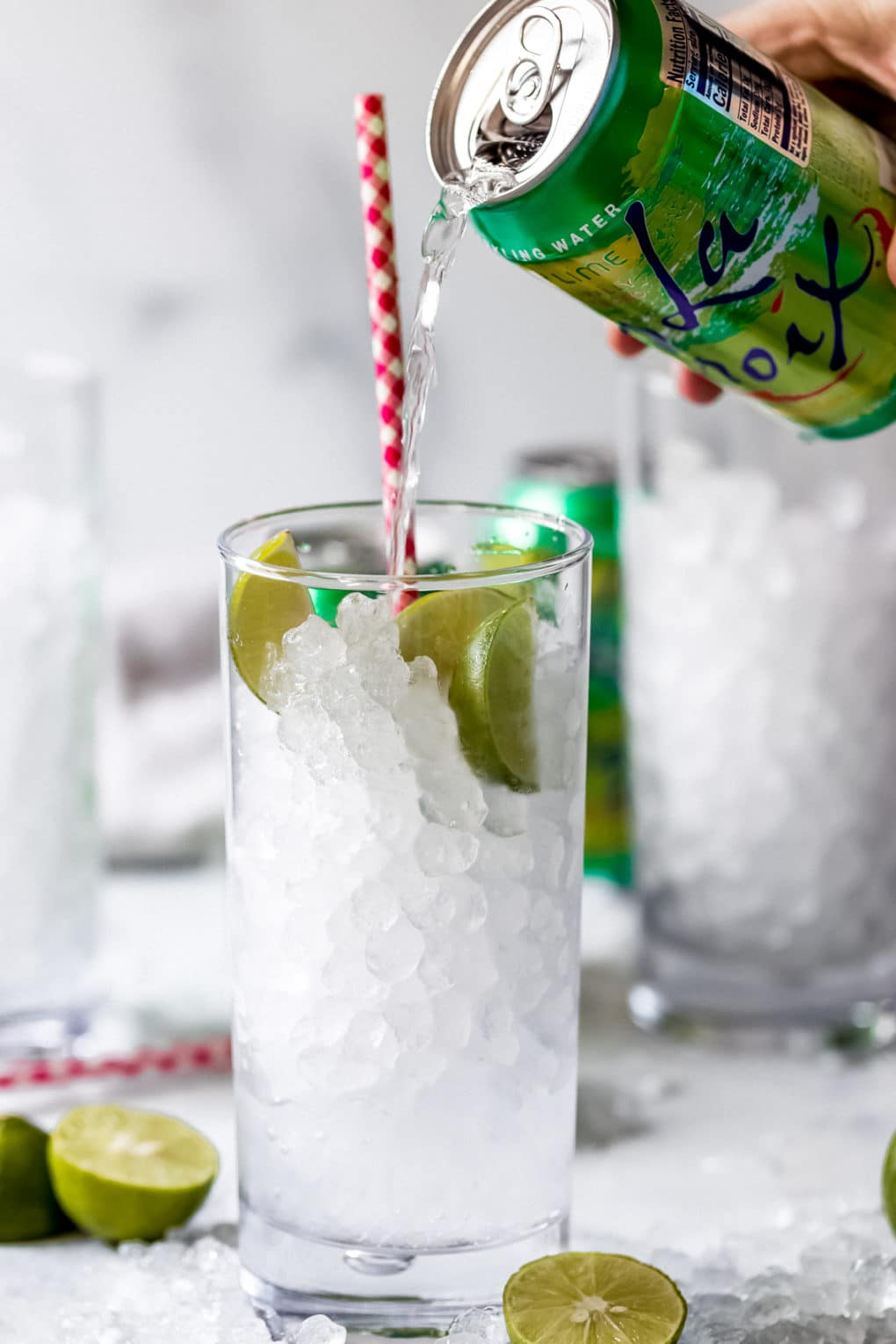 a woman pouring La Croix key lime sparkling water into a highball glass with ice and key limes