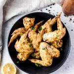 a bowl of lemon pepper chicken wings