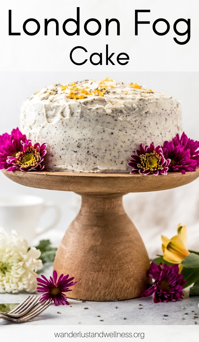 a london fog cake on a wooden cake stand with purple flowers around it