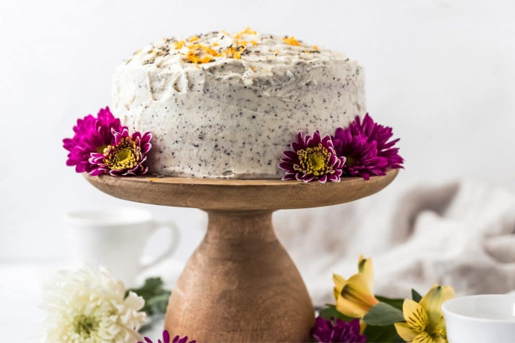 a London fog cake on a wooden cake stand with purple flower around it