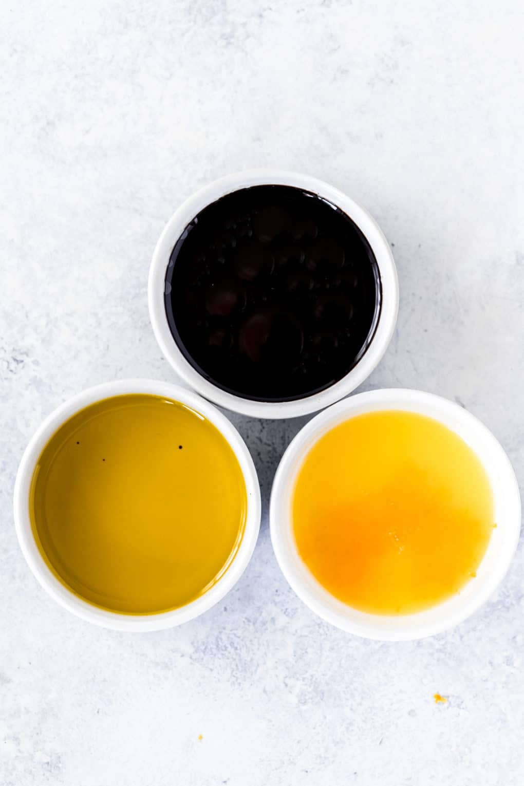 3 small white bowls with ingredients for a citrus vinaigrette dressing