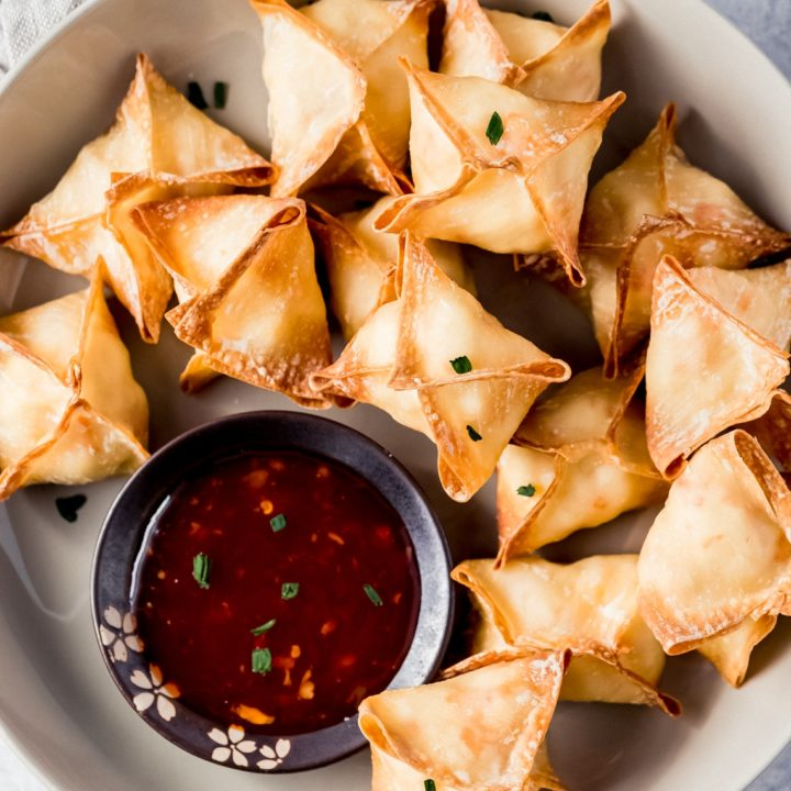 a bowl of crab rangoon with dipping sauce