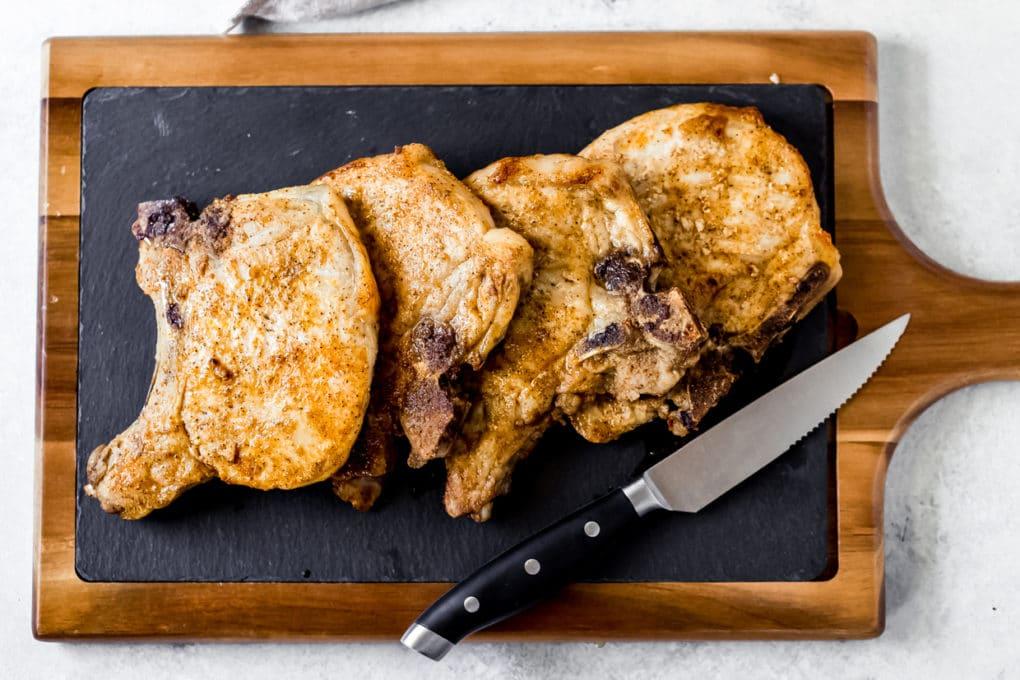 four cajun air fryer pork chops on a cutting board