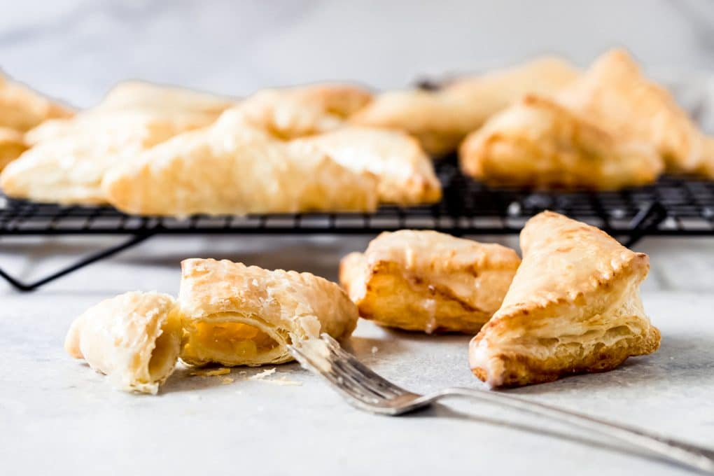 air fryer apple turnovers on a cooling rack, one cut open with a fork