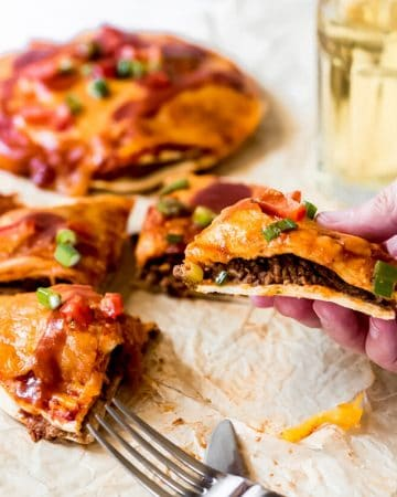 a woman holding a slice of air fryer Mexican pizza
