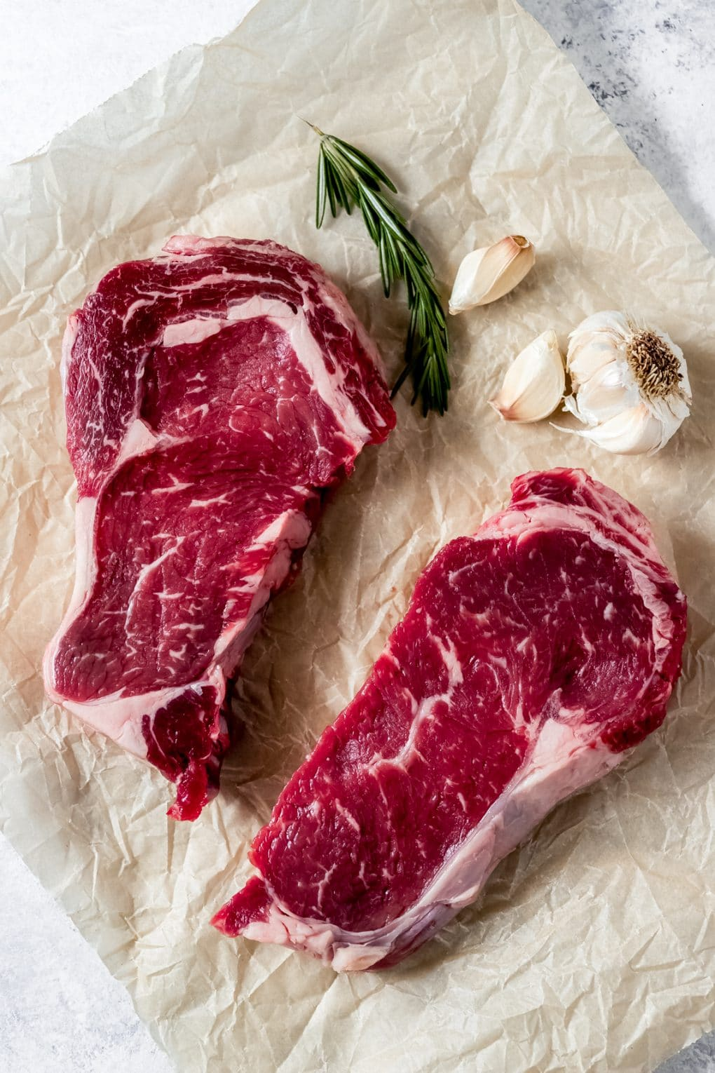 two raw ribeye steaks and rosemary and garlic on a table