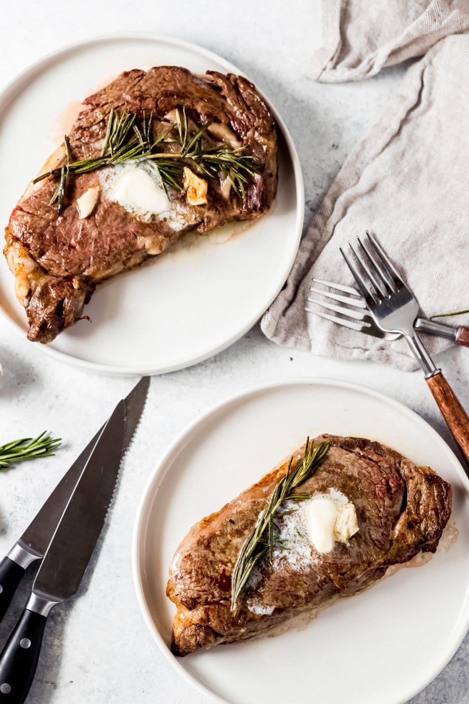 two air fryer ribeye steaks on plates