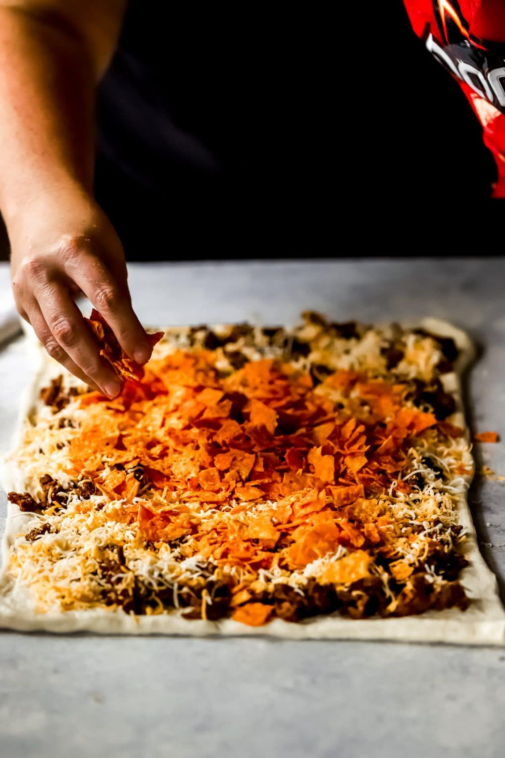 a woman adding crushed Doritos to unbaked Doritos pizza rolls