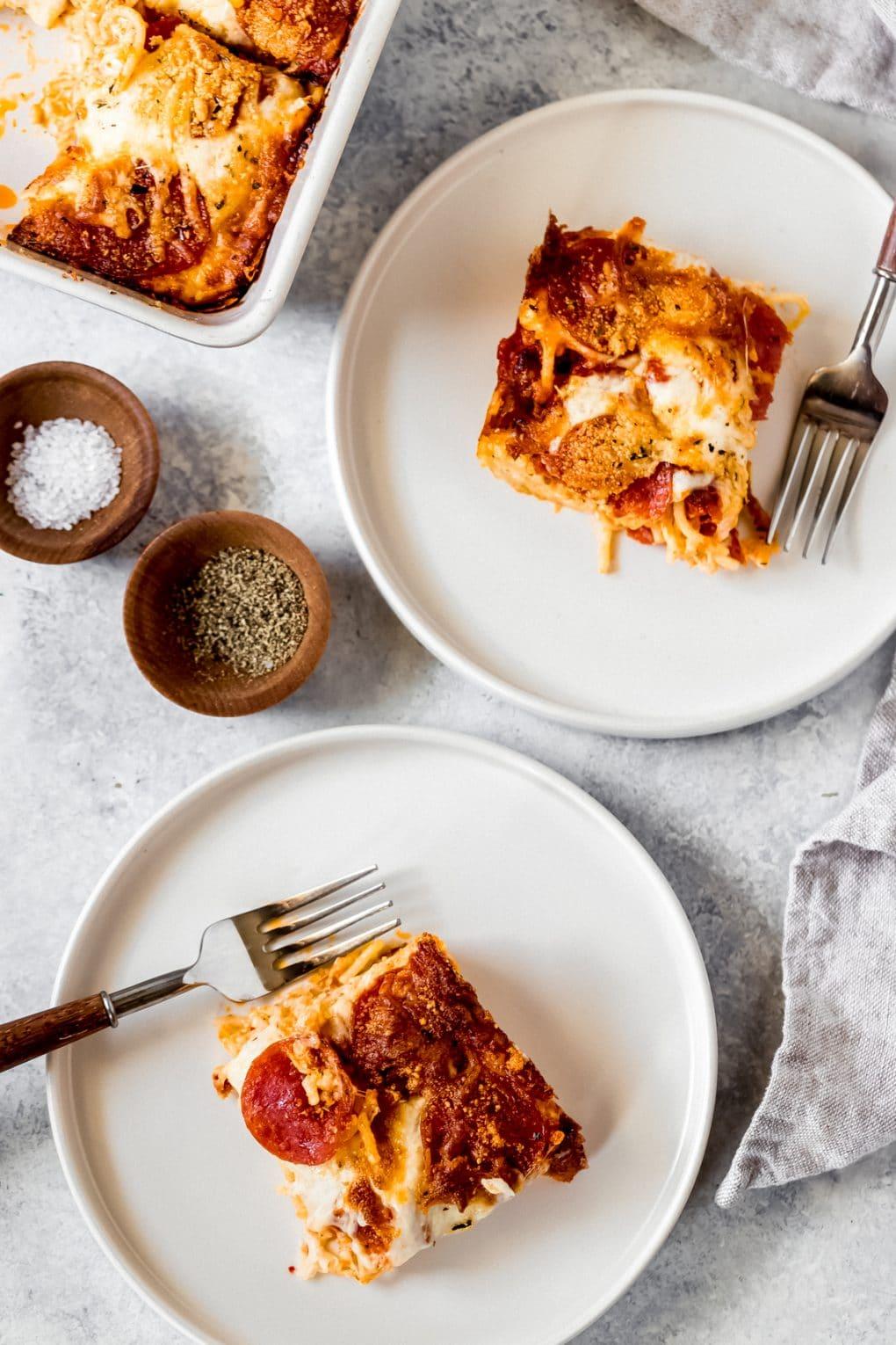 two servings of pizza baked spaghetti on white plates
