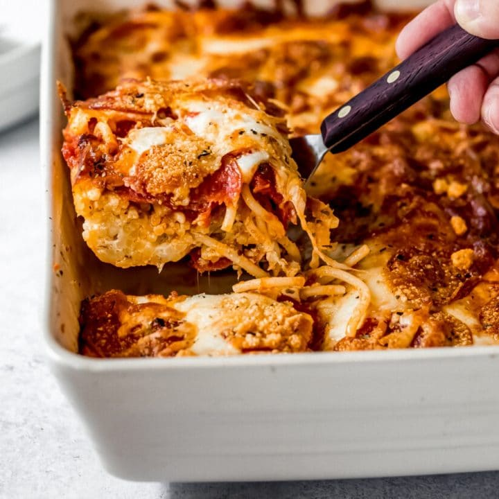 a person serving a slice of pizza baked spaghetti