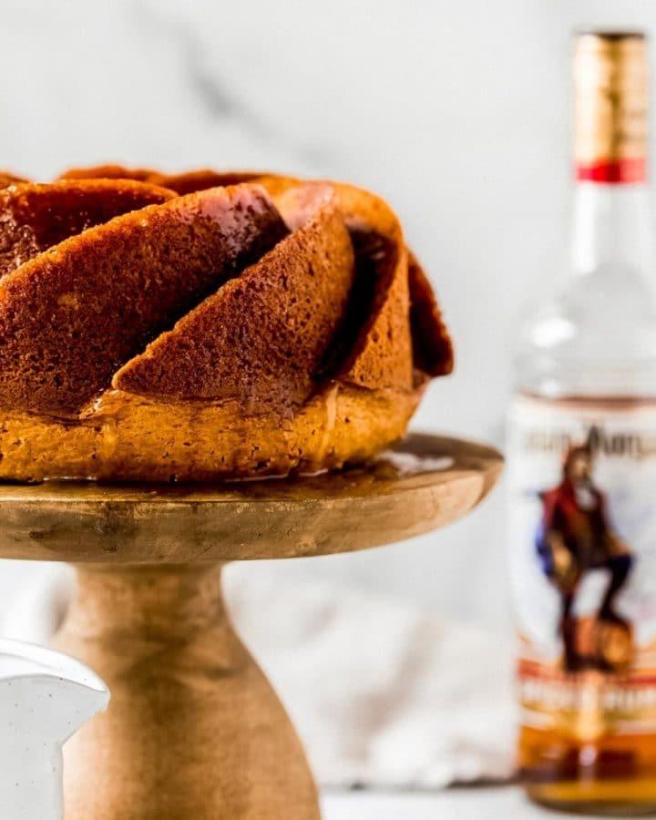 a rum cake on a wooden cake stand