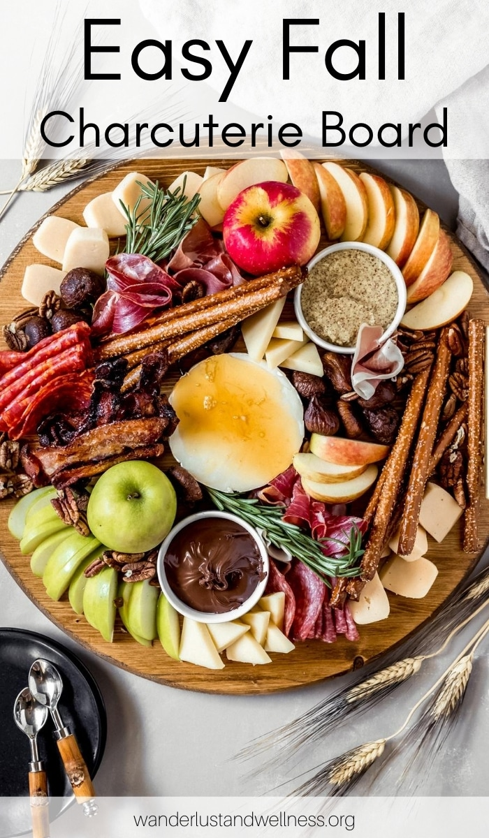 a round fall charcuterie board filled with meats, cheese, and seasonal fruits and condiments