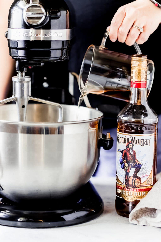a woman pouring rum into a mixer