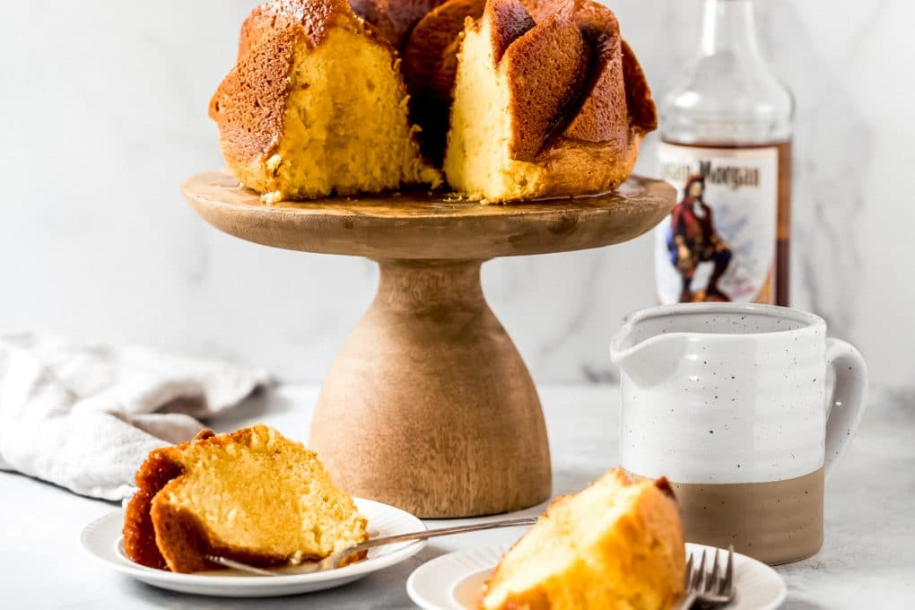 an easy rum cake on a cake stand with two slices served on plates