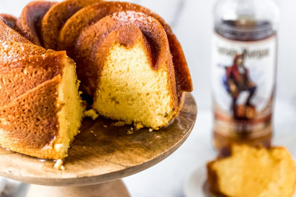 a rum cake on a cake stand with two slices missing