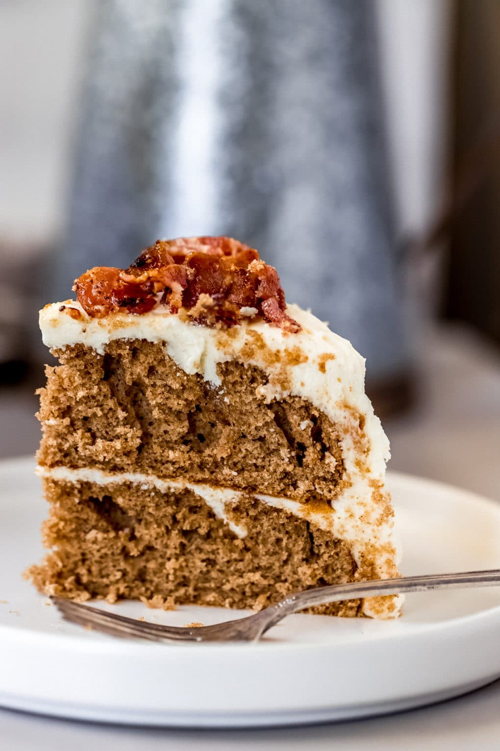 a slice of maple bacon cake on a white plate