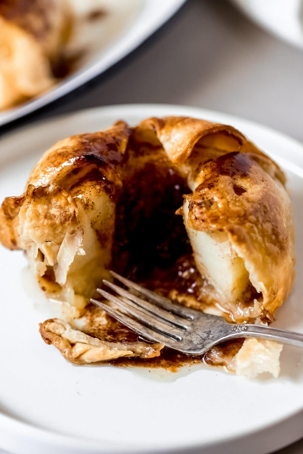 an air fryer apple dumpling on a plate with a fork