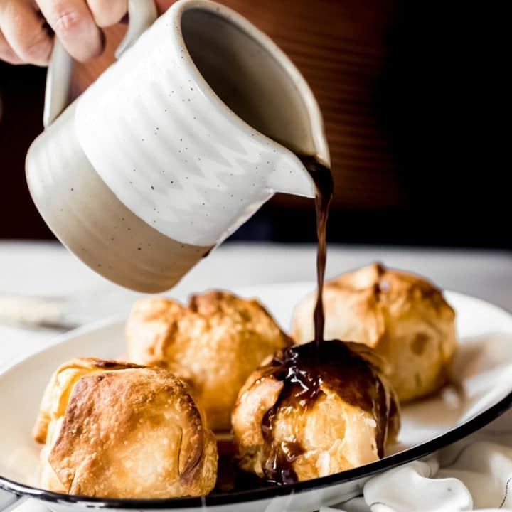 a woman pouring a glaze over air fryer apple dumplings