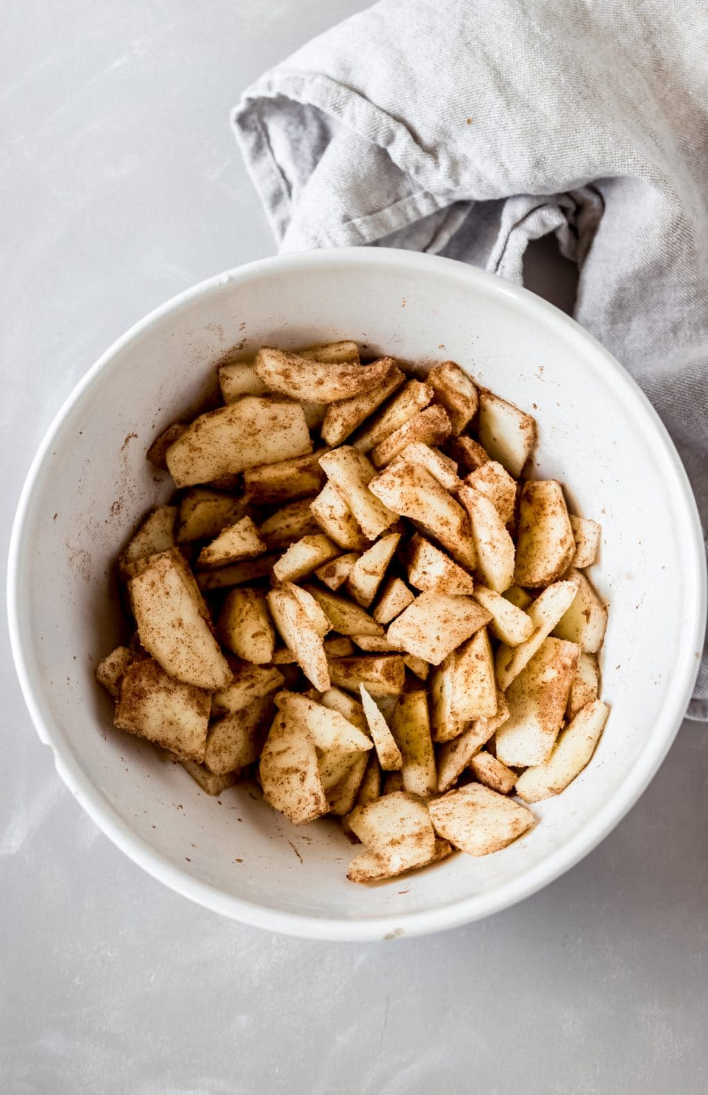 a bowl of sliced apples mixed with cinnamon and sugar