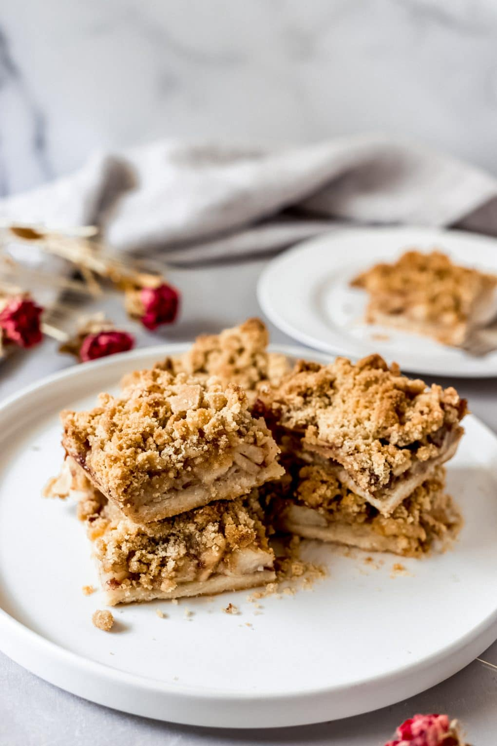 four apple pie shortbread bars stacked on a white plate
