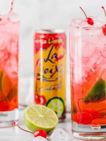 two glasses of cherry lime la croix cocktail with a can of La Croix Cerise Limon