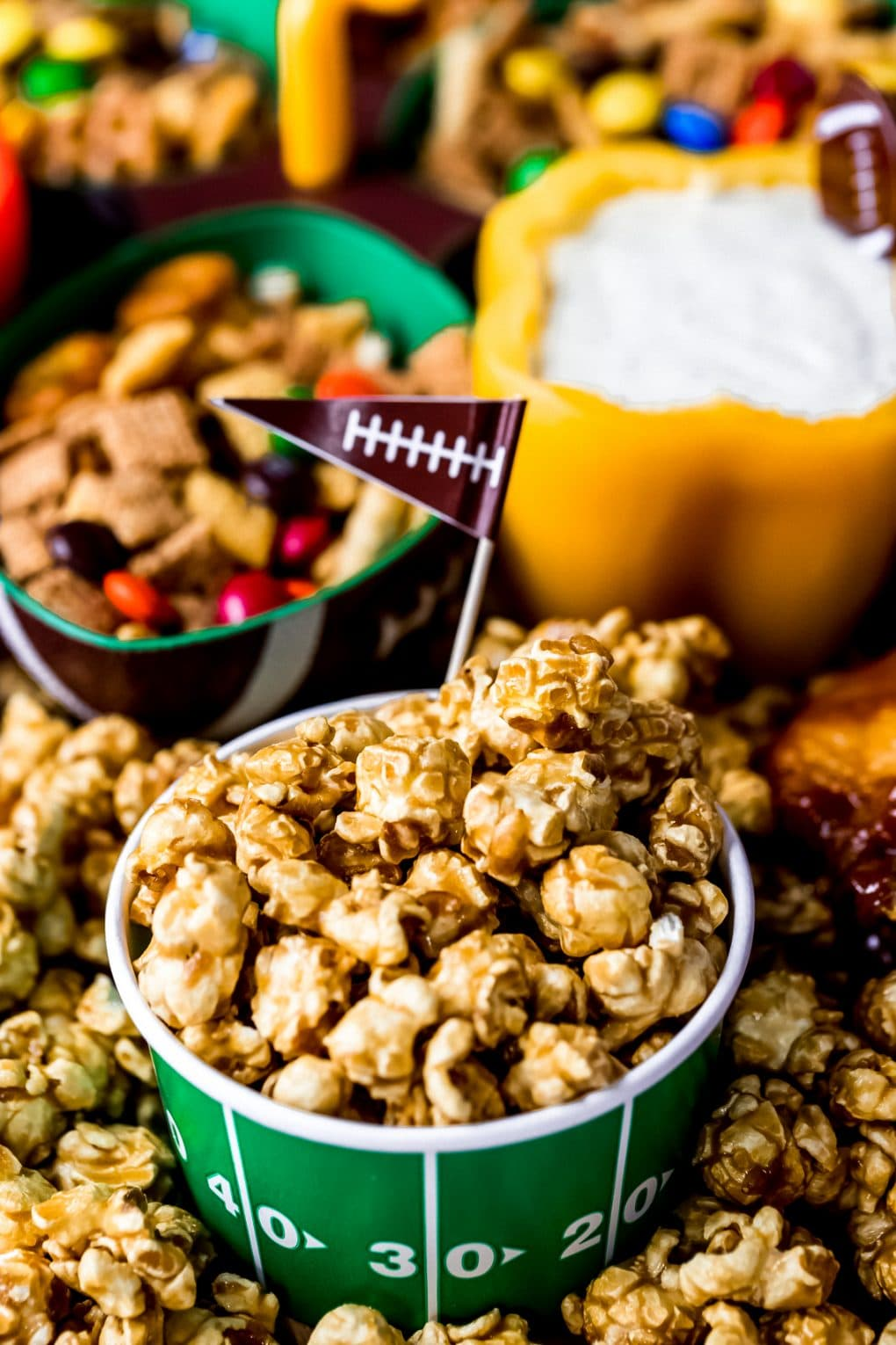 a bowl of caramel popcorn on a game day charcuterie board
