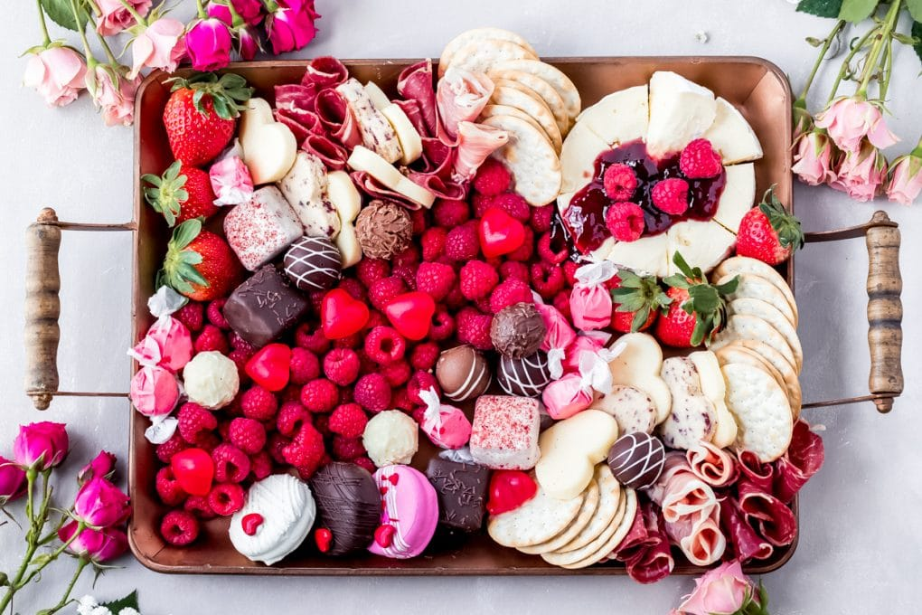 a valentine charcuterie board filled with savory meats and cheese and sweet desserts