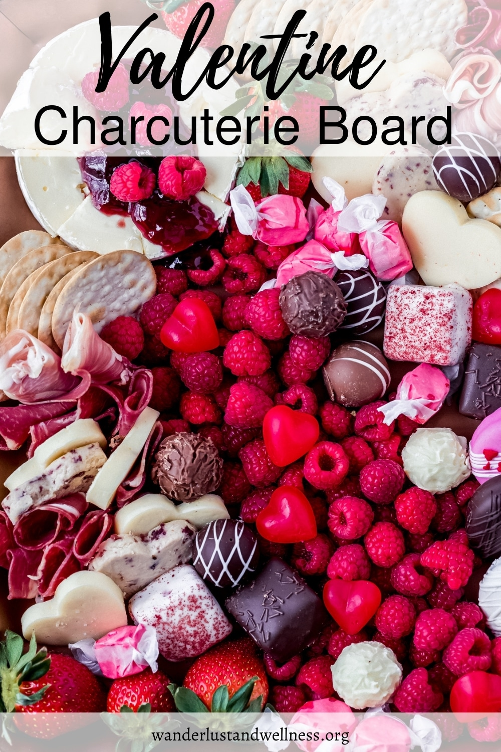 a valentine's day charcuterie board filled with savory meats and cheese and sweet desserts