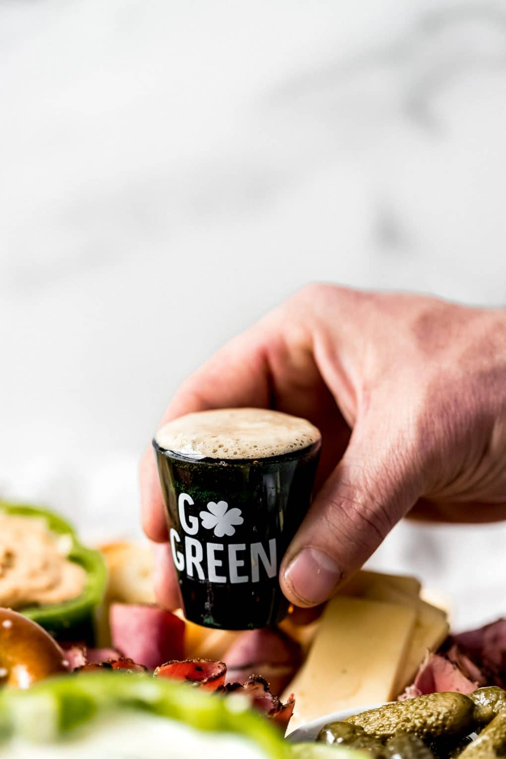 a shot glass of Guinness beer on a St. Patrick's Day charcuterie board
