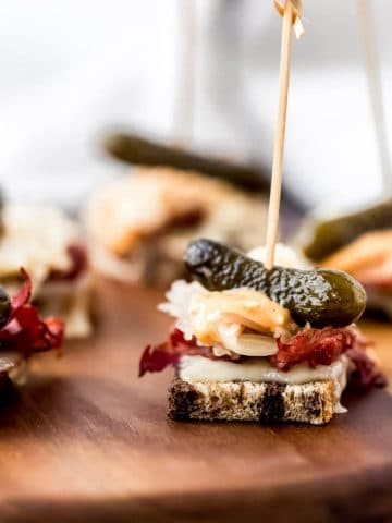 several mini reuben party appetizers on a platter