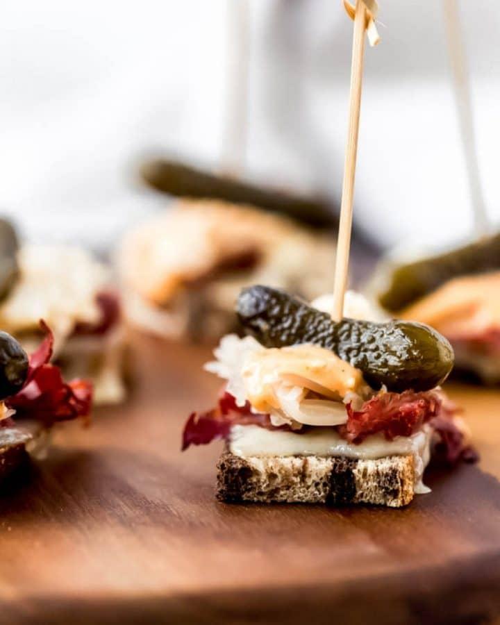 several mini reuben party appetizers on a platter