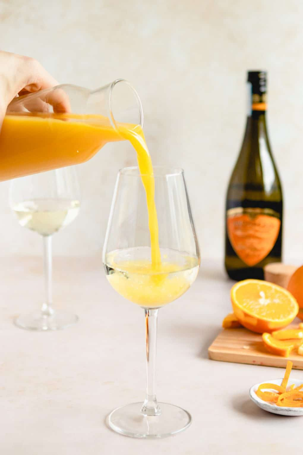 pouring orange juice into a glass for a classic mimosa