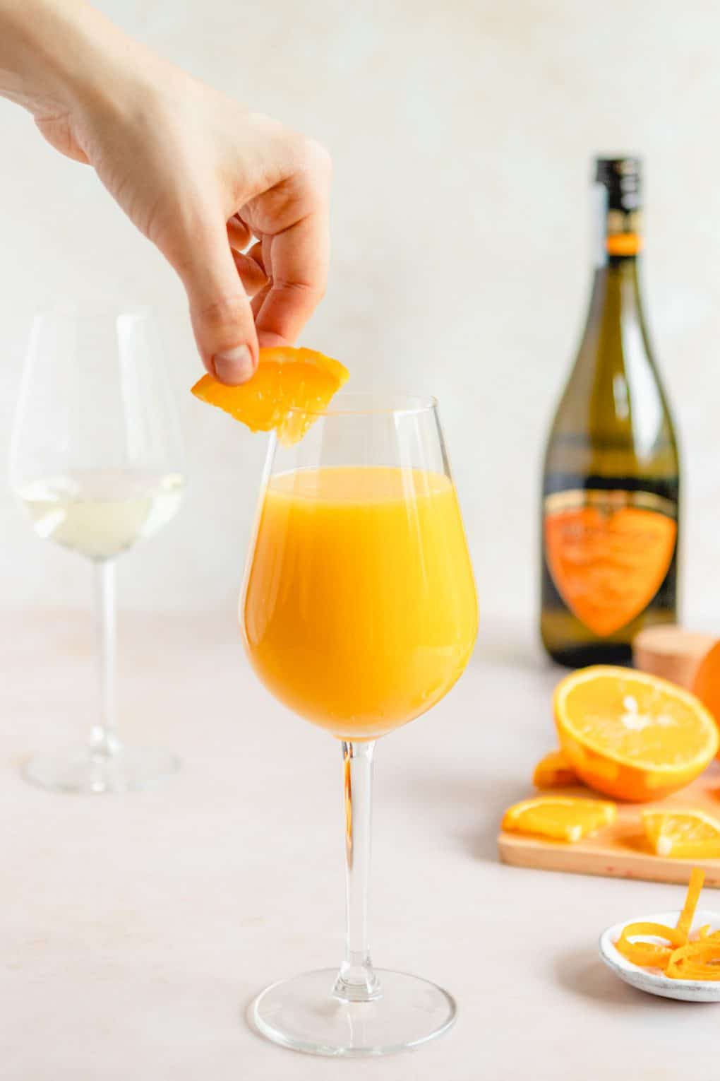 someone garnishing a classic mimosa glass with a slice of orange