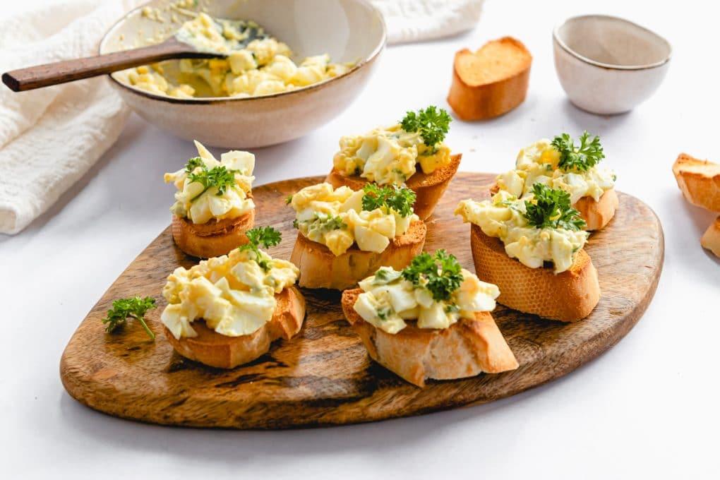 egg salad crostini on a cutting board