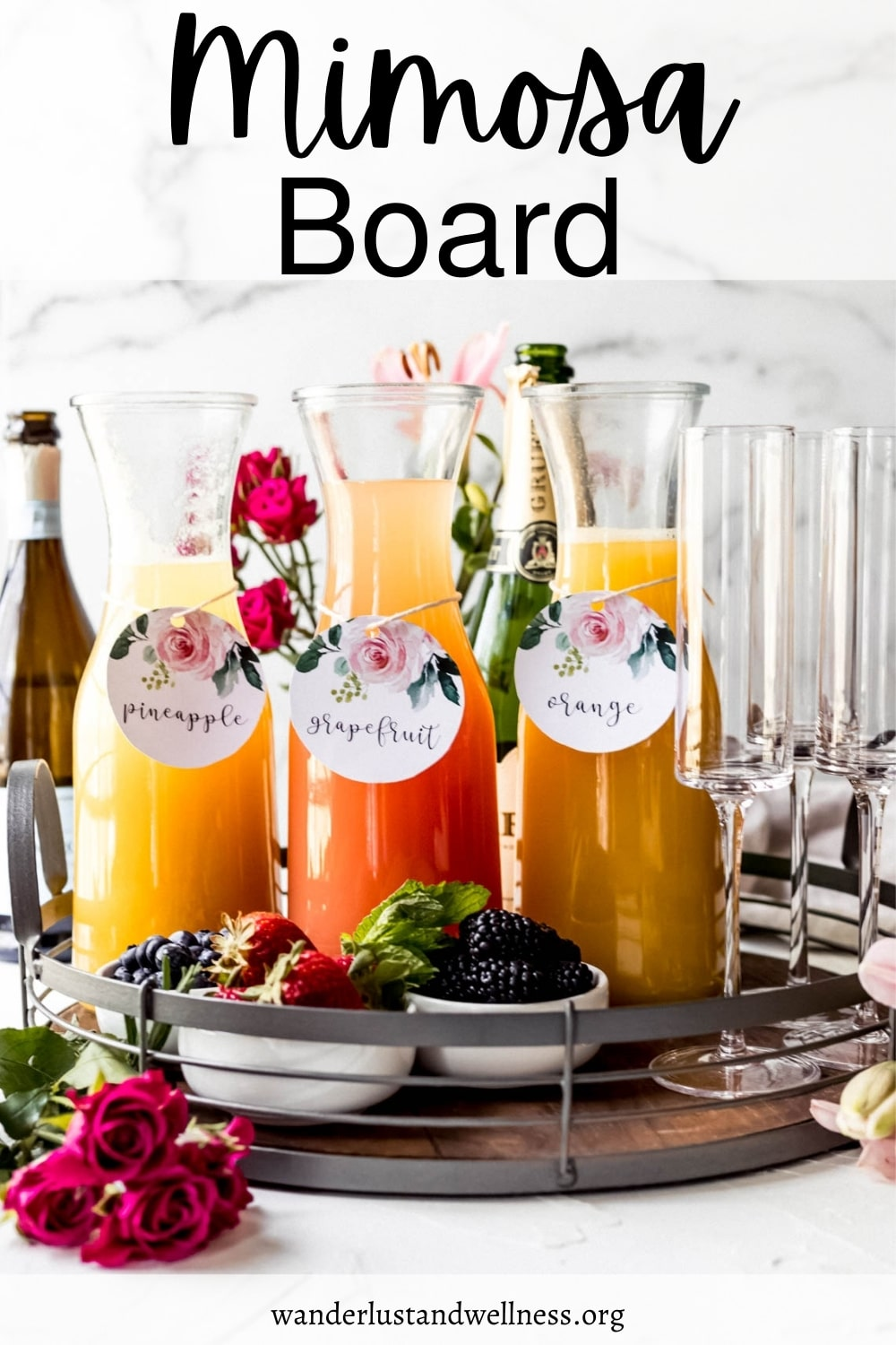 three glass carafes of mimosas on a mimosa board