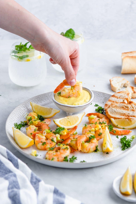 a woman dipping shrimp into a dijon sauce