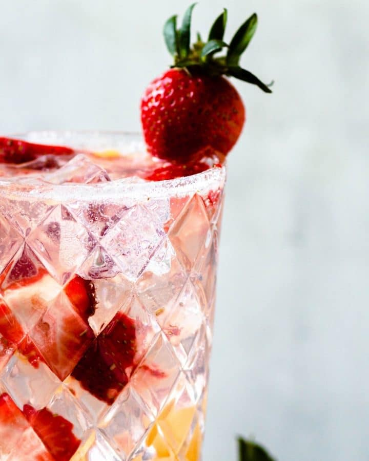a tall glass of a pineapple strawberry cocktail with fresh strawberries