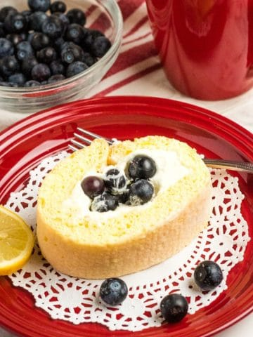 red plate with lemon roll on top
